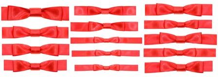 Satz rote Bogenknoten auf schmalen Satinbändern Stockbilder
