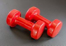 Satz rote Handgewichte, Dummköpfe, liegend auf einem schwarzen Übung yo Lizenzfreies Stockbild