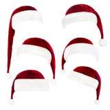 Satz rote Santa Claus-Hüte lokalisiert auf Weiß Stockfotografie
