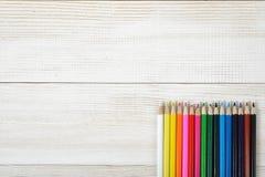 Satz scharfe bunte Bleistifte sind in Folge auf hölzernem leerem Brett Lizenzfreies Stockbild