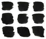 Satz schwarze Aquarellhandpinselanschläge werden auf einem weißen Hintergrund lokalisiert. Stockbild