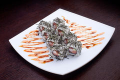 Satz Sushi maki mit Krabbe und süßer Soße auf weißer Platte Japanisches Lebensmittel auf Hintergrund Stockfoto