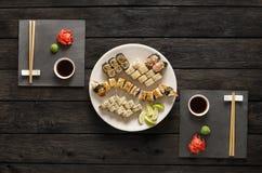 Satz Sushi maki und Rollen auf schwarzem rustikalem Holz, Draufsicht Stockfoto