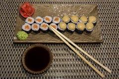 Satz Sushirollen Hosomaki auf einer rechteckigen stilisierten Platte stockfotografie