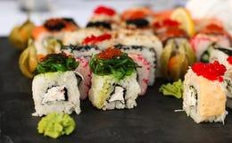 Satz Sushirollen mit vasabi und Ingwer auf einer dunklen Schieferplatte lizenzfreie stockfotos