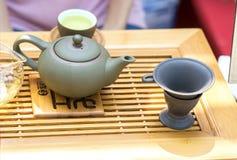 Satz Teekannen und die alte Teeschale auf dem Tisch ausgestellt Lizenzfreie Stockbilder