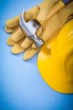Satz Tischlerhammerschutzhandschuhe, die Sturzhelm auf blauem backgro errichten Lizenzfreies Stockfoto