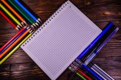 Satz unterschiedliches Schulbriefpapier Notizblock, pensils, auf woode Lizenzfreie Stockfotos