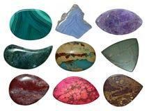 Satz verschiedene bunte Steine lokalisiert auf einem Weiß Lizenzfreie Stockfotos