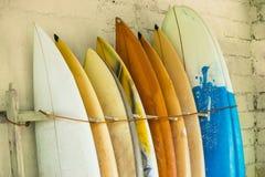 Satz verschiedene Farbbrandungsbretter in einem Stapel durch Ozean Bali, Indo lizenzfreies stockbild