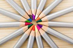 Satz verschiedene farbige Bleistifte auf hölzernem Schreibtisch Lizenzfreies Stockbild