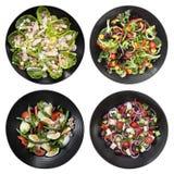 Satz verschiedene Salate auf weißem Hintergrund Stockfotografie