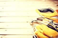 Satz verschiedene Werkzeuge auf hölzernem Hintergrund Goldtasten in den Fingern mit Häusern Stockfotos
