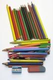 Satz von alten farbigen Bleistiften, von zwei Bleistiftspitzern und von bilateralem Radiergummi Lizenzfreies Stockfoto