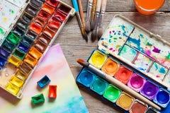 Satz von Aquarellfarben, von Bürsten für das Malen und von Papierblatt Lizenzfreie Stockfotos