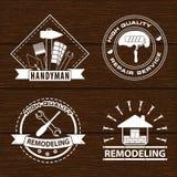 Satz von den Hauserneuerungsaufklebern und -haus, die Logos umgestalten Heimwerkerlogo auf hölzernem Hintergrund Lizenzfreie Stockfotografie