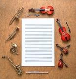 Satz von fünf goldener Blechbläser und vier reihen Orchestermusikinstrumente und -Noten auf, die zwischen ihnen liegen Lizenzfreies Stockbild