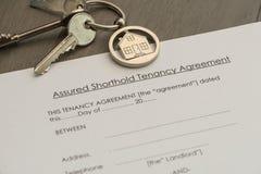 Satz von Schlüsseln und von Mietvertragdokument stockbild