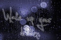 Satz wachen Ihre Träume auf, die auf ein nasses Glas geschrieben werden Nachtstadtleben durch Windfang: Dunkelheit und Regen Stockfoto