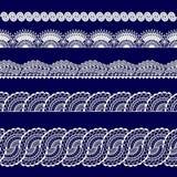 Satz weiße Spitzebänder auf einem blauen Hintergrund Stockfotografie