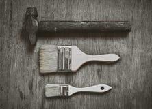 Satz Werkzeuge: eine große Bürste, zum einer kleinen Bürste, um zu malen und der alten Hammernägel auf hölzernem Hintergrund zu m Lizenzfreie Stockbilder
