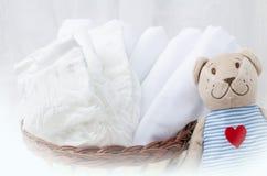 Satz Windeln für neugeborenes im Korb mit Liebesbärnspielzeug Babycl Stockfoto
