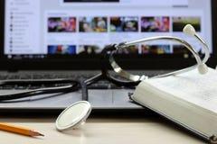 Satzrechner, Stethoskop und Buch auf einem Desktop Lizenzfreie Stockfotografie