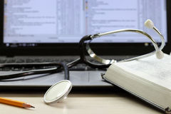 Satzrechner, Stethoskop und Buch auf einem Desktop Lizenzfreies Stockbild