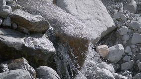 Sauber, Gebirgstrinkende Wasserströme unten von einem großen Stein stock video