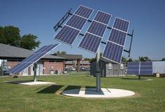 Saubere Energie-Solarenergie-Gremiums-Reihen und blauer Himmel mit grünem Gras Stockfotografie