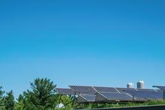 Saubere Energie: Sonnenkollektoren auf einem Hintergrund des klaren blauen Himmels und des grünen Grases Konzept der alternativen Lizenzfreie Stockbilder