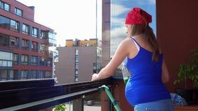 Saubere Glasfenster des schwangeren weiblichen Mädchens in der Loggia stock video