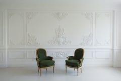 Sauberer heller weißer Luxusinnenraum mit Stühlen eines alten antiken Weinlesegrüns über Wandgestaltungsflachrelief-Stuckformteil Stockfotografie