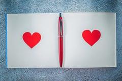 Sauberer Notizblock des roten Herzen Biro-Stiftes auf metallischem Hintergrund educati stockbild