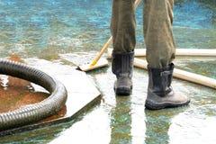 Sauberere Stiefel des Pools oder des Brunnens, Bürste entfernt Rückstand von der Oberfläche, gewölbten Schlauch lizenzfreie stockbilder