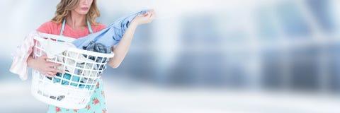 Saubererer haltener Wäschekorb mit hellem Hintergrund Lizenzfreie Stockbilder
