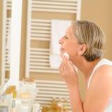 Sauberes Gesicht der älteren Frau mit Baumwolauflage Lizenzfreies Stockfoto
