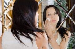 Sauberes Gesicht der Frau, das Spiegel schaut Lizenzfreies Stockfoto