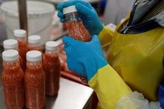 Sauce à ajika d'emballage dans une usine de traitement des denrées alimentaires des produits alimentaires images stock