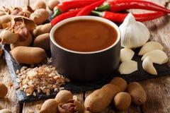 Sauce épicée douce et aigre à tamarinier avec des ingrédients en gros plan sur une table horizontal photo libre de droits