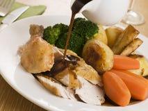 Sauce au jus étant renversée au-dessus d'une plaque de poulet rôti photos stock