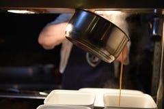 Sauce au jus de cuisson à la vapeur chaude se renversante d'une casserole dans un plat avec l'espace photographie stock libre de droits