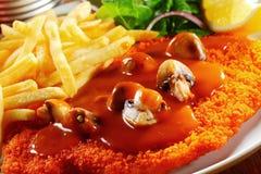 Sauce au jus sur Jaegerschnitzel avec des champignons appareillés avec des fritures Photos stock