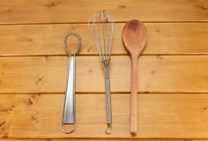 Sauce and balloon whisks and wooden spoon Stock Photography