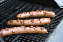 Hot Dogs and Ketchup on Outdoor Grill. Outdoor grill with hot dog sausages covered in barbecue sauce Stock Photo