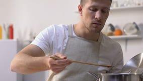 Sauce de essai à homme dans la casserole et vissage vers le haut du visage en raison du mauvais goût, faisant cuire banque de vidéos