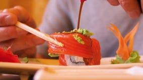 Sauce de soja de versement d'homme sur le petit pain de sushi et consommation dans le restaurant japonais clips vidéos