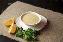 Sauce in einer Platte, Majonäse in einer Platte, selbst gemachte Soße, Soße Caesar, eine Zitrone, Grüns Lizenzfreie Stockbilder