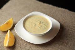 Sauce in einer Platte, Majonäse in einer Platte, selbst gemachte Soße, Soße Caesar, eine Zitrone, Grüns Stockfoto