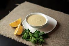 Sauce in einer Platte, Majonäse in einer Platte, selbst gemachte Soße, Soße Caesar, eine Zitrone, Grüns Stockfotos